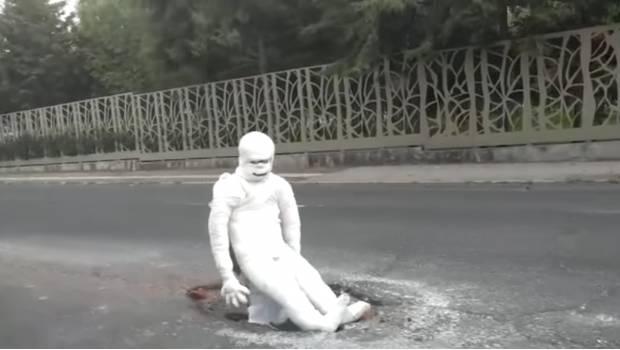 """Photo of #Vídeo Momia """"Asusta"""" A Automovilistas Para Que No Caigan En Bache"""